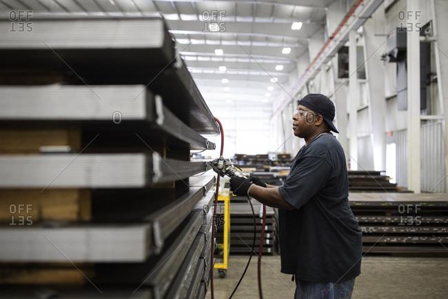 Side view of worker working on metal sheets in Steel Industry Factory