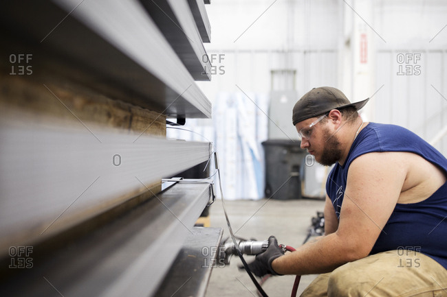 Side view of man working on metal sheets while crouching