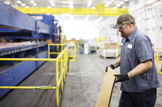 Smiling worker holding metal sheets while working in Steel Industry Factory