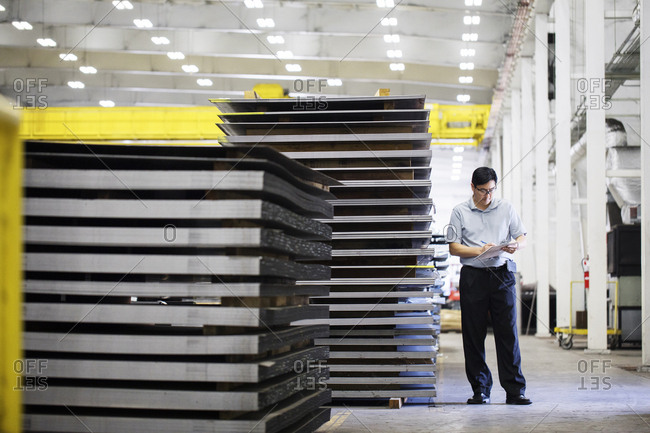 Mature manager examining metal sheets while standing at warehouse