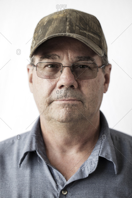 Portrait of serious manual worker wearing cap against white background