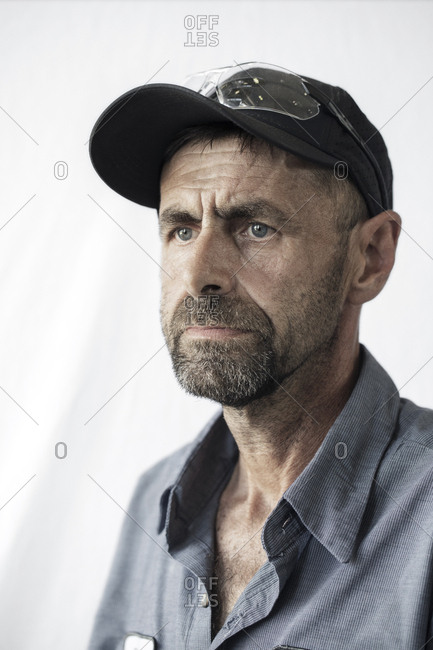 Thoughtful manual worker looking away against white background