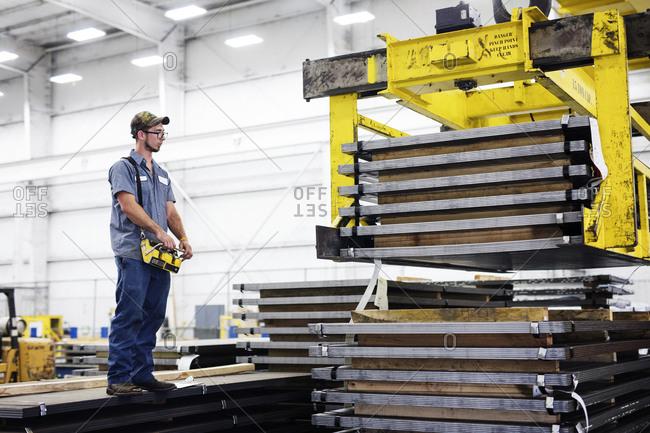 Worker operating overhead crane in metal Steel Mill