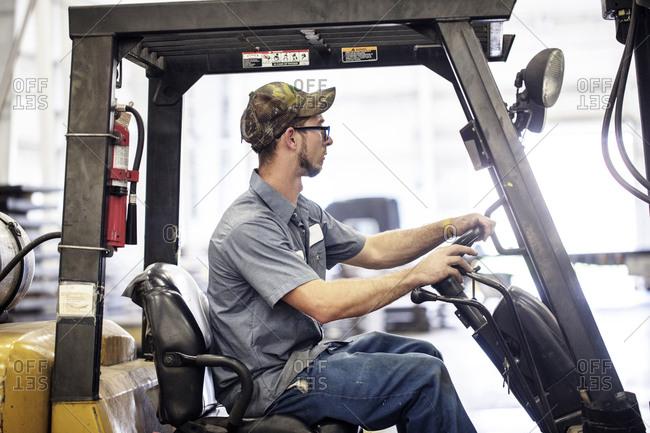 Side view of manual worker driving forklift in metal Steel Industry Factory