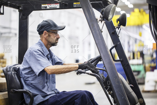Side view of manual worker driving forklift while working in metal Steel Industry Factory