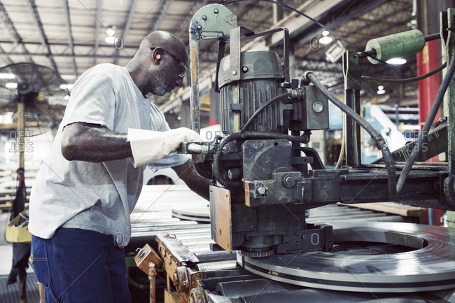 Side view of blue collar worker using machine for tying steel in factory