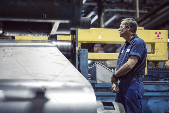 Manual worker looking at machine manufacturing sheet steel in factory