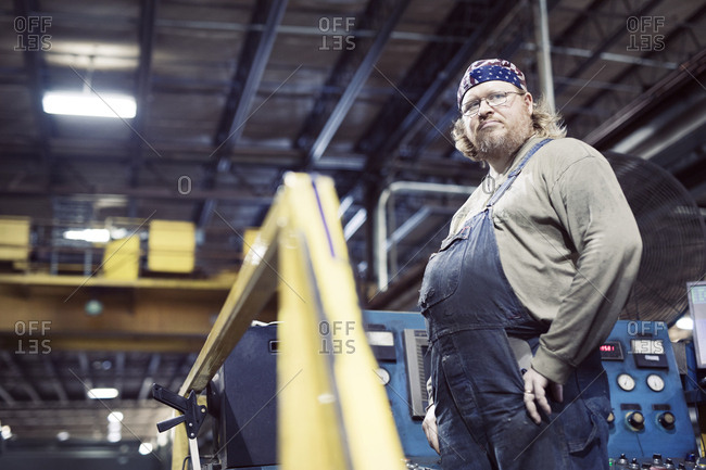 Low angle view of blue collar worker wearing bib overalls and headscarf while working in steel industry