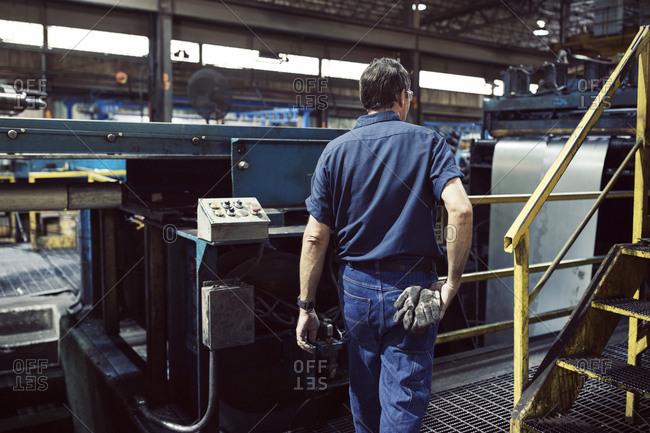 Rear view of blue collar worker working in steel industry