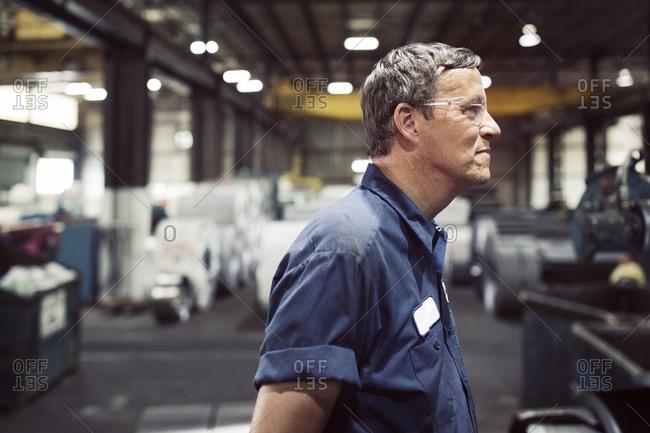 Side view of blue collar worker looking away in steel industry