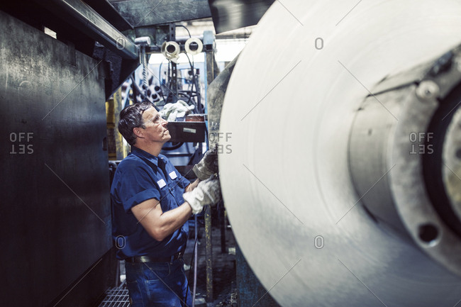Worker using machine while working in steel mill