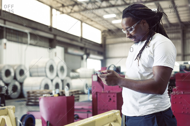 Manual worker using smart phone while standing in steel industry