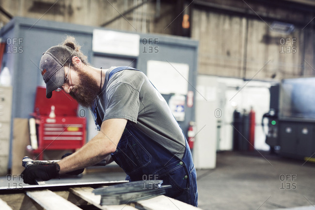 Manual worker using hammer and chisel in steel factory