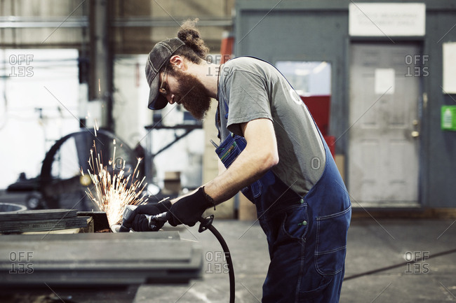 Side view of welder working in steel industry