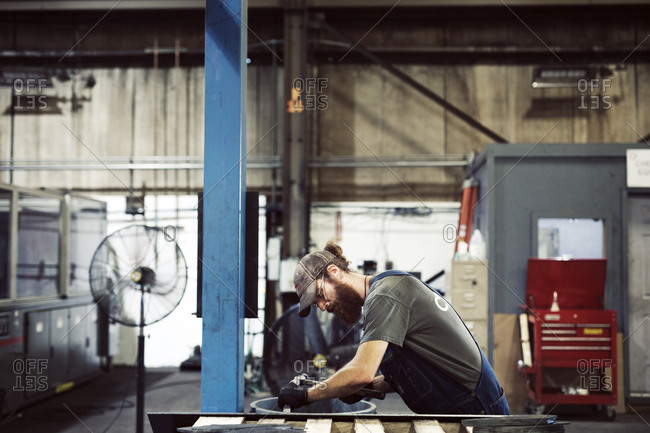 Side view of blue collar worker using hammer and chisel in steel factory