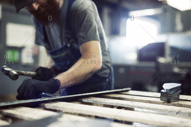 Midsection of blue collar worker using hammer and chisel in steel factory