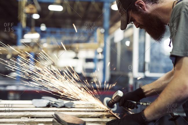 Manual worker using welding machine in steel factory