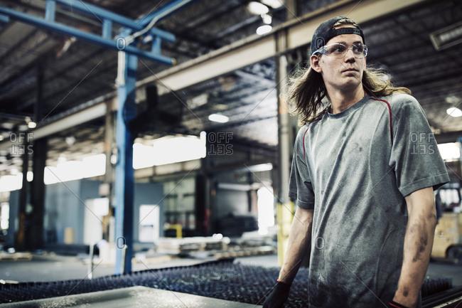 Manual worker looking away while standing in steel factory
