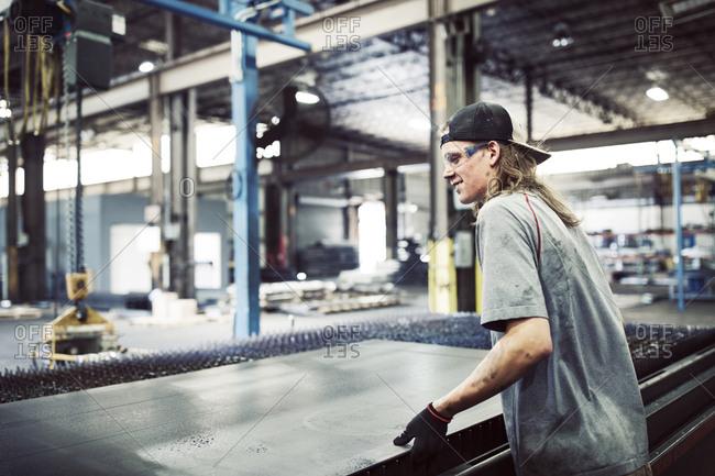 Side view of steel worker working in steel factory
