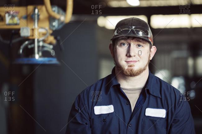 Portrait of confident blue collar worker wearing cap in steel factory