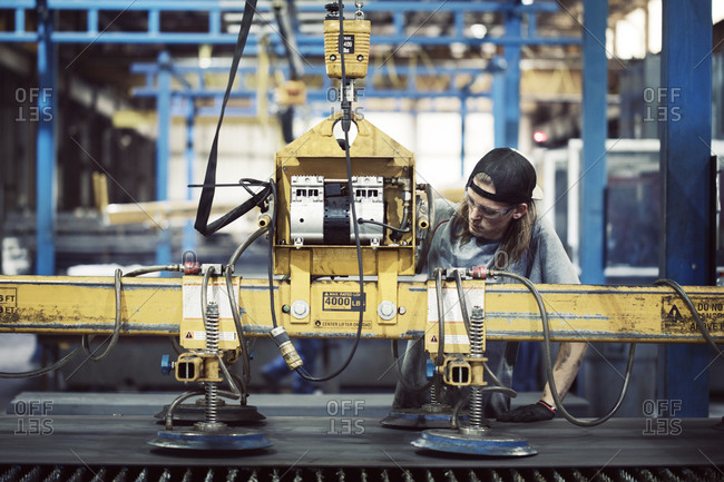 Steel worker examining machinery while working in factory