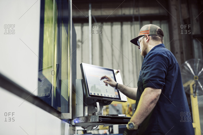 Low angle view of blue collar worker using desktop computer while working in steel factory