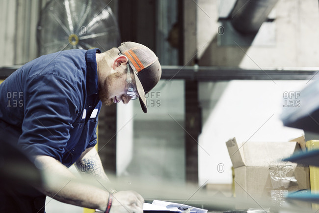 Side view of serious blue collar worker working in workshop