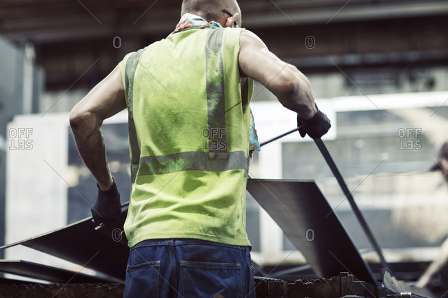 Rear view of blue collar worker using machinery while manufacturing sheet steel in industry