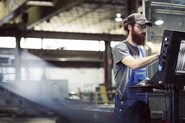 Manual worker wearing cap while using desktop computer in steel industry