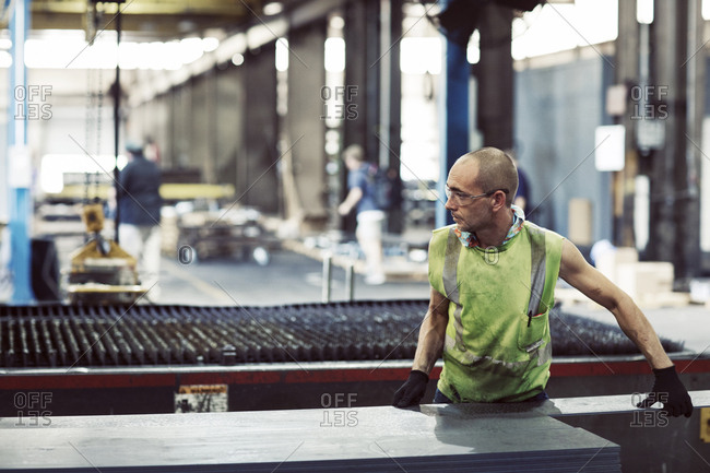 Manual worker using machinery while manufacturing sheet steel in industry
