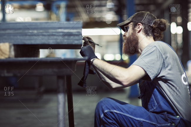 Serious male worker working on sheets at steel factory