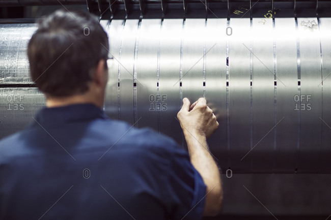 Rear view of worker analyzing steel sheets at industry