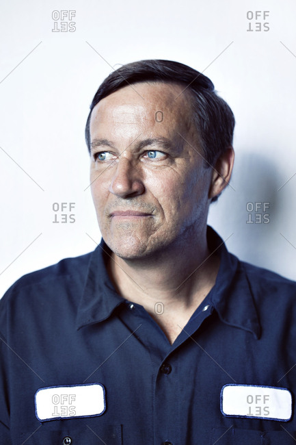 Close-up of thoughtful worker looking away against white background