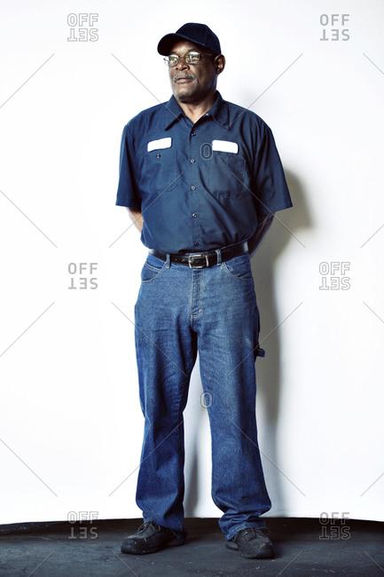 Full length of senior worker standing against white backdrop