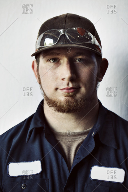 Portrait of young worker wearing cap against white background