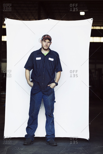 Full length portrait of young worker standing with hands in pockets against white backdrop