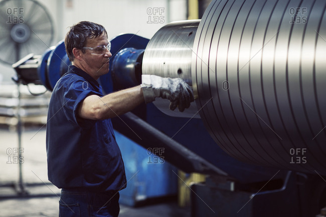 Mature worker examining in steel sheets rolling on machine at industry