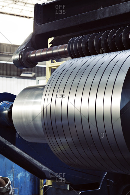 Close-up of steel sheets spinning on machine at industry