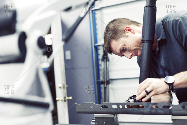 Serious male worker working on steel with machine at industry