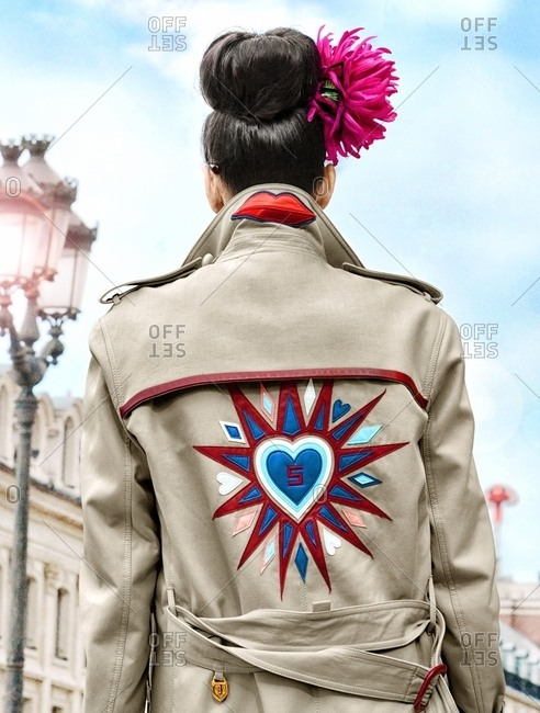 Paris, France - July 3, 2017: Rear view of woman wearing tan coat with hears and lips
