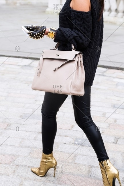 London, England - February 28, 2015: Woman dressed in black and gold