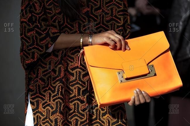 London, England - February 29, 2016: Stylish woman holding orange handbag