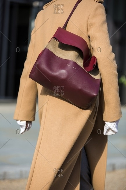 London, England - February 29, 2016: Stylish woman wearing tan coat and carrying a burgundy bag