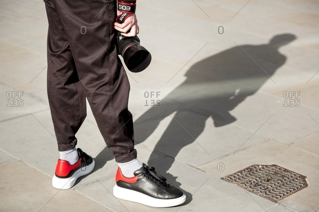 London, England - February 29, 2016: Fashionable photographer and shadow