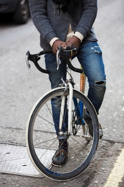 London, England - February 29, 2016: Man on a bicycle wearing ripped denim jeans