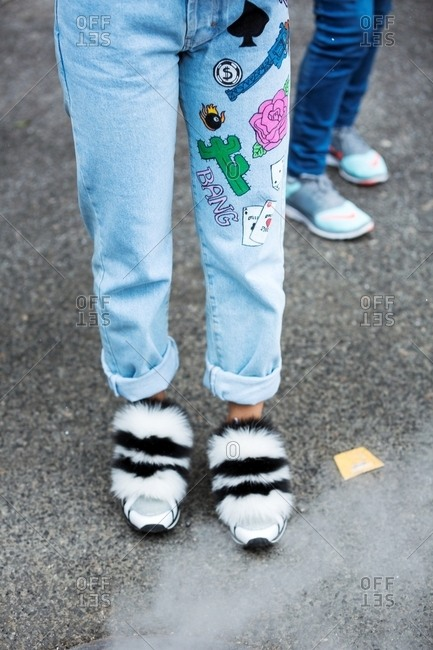 New York - February 29, 2016: Woman wearing light denim jeans and furry shoes