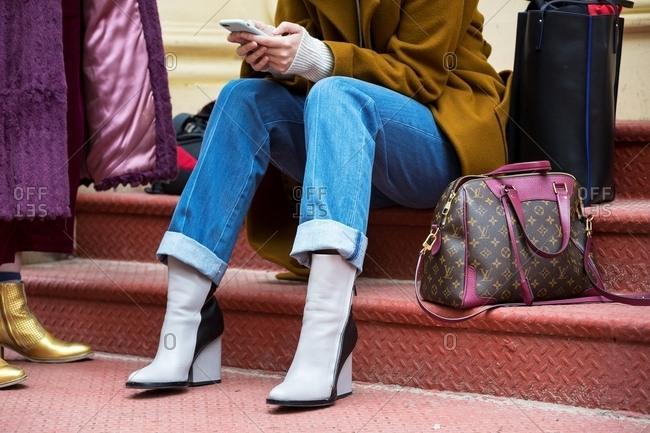 New York - February 29, 2016: Stylish woman sitting on steps using phone