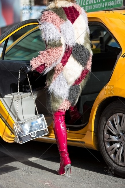 New York - February 29, 2016: Woman wearing furry coat getting into a cab