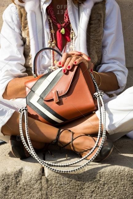 Paris, France - November 4, 2016: Fashionable woman sitting on cross-legged holding designer purse