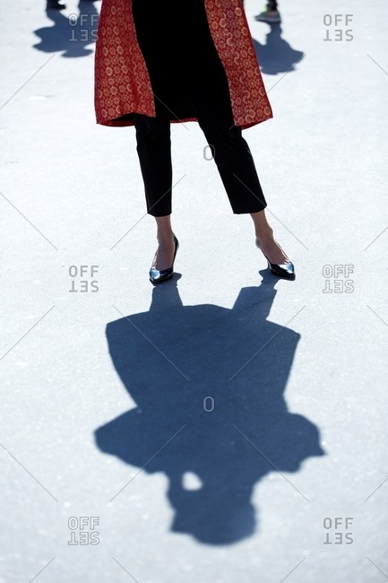Paris, France - November 4, 2016: Shadow of woman wearing red coat and pumps